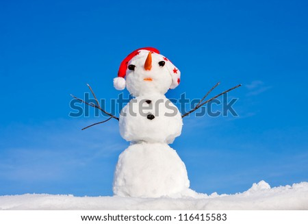 Snowman in santa cap on nature in sunny cold day