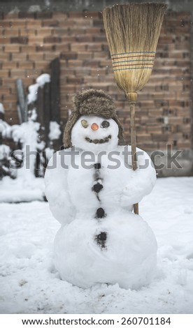 Snowman in the yard holding a broom - stock photo