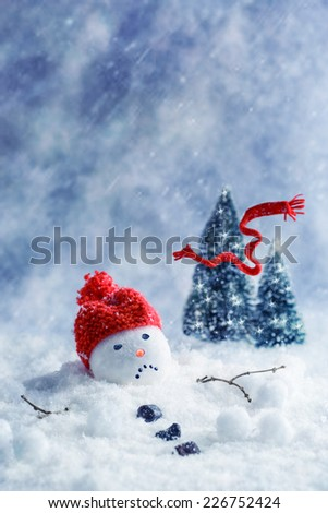 Snowman melting with scarf blowing away into Christmas trees - stock photo