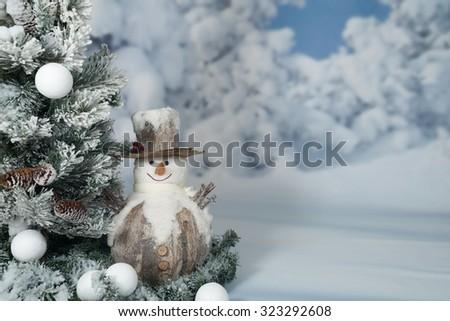 Snowman next to Christmas tree - stock photo