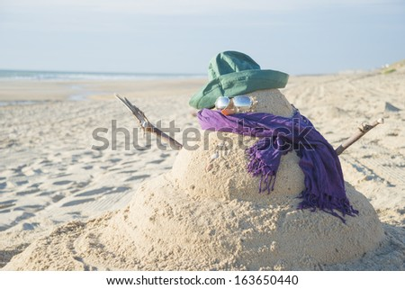 Snowman on beach with shells as mouth, sun glasses,hat and scarf - stock photo