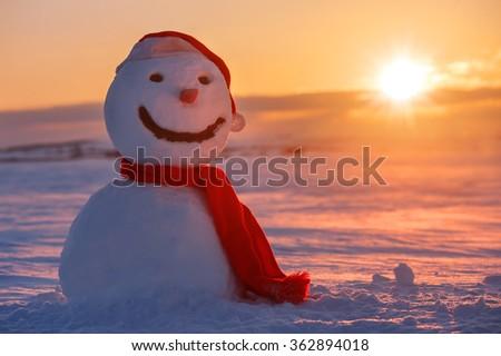 snowman on orange sunset background - stock photo
