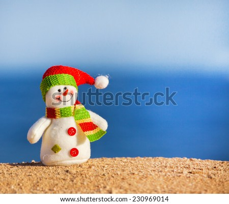 Snowman on sand near sea. Christmas decoration. Vacations - stock photo