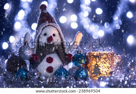 Snowman smiling brought Christmas balls, blue background with flashing lights snowing - stock photo