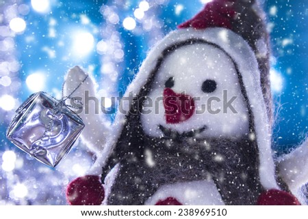 Snowman Smiling brought Christmas gifts, turquoise background snowy landscape - stock photo