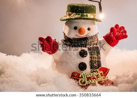 Snowman stand among pile of snow at silent night with a light bulb, light up the hopefulness and happiness in Merry christmas and happy new year night.