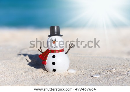 Snowman toy at white sandy beach on Caribbean sea background