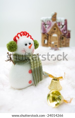 Snowman with bells standing in front of the house.