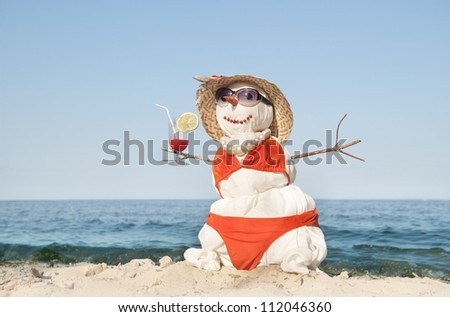 Snowman with cocktail at the beach - stock photo
