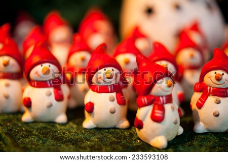 Snowman with red scarf and hat. Snowman figurine, statuette. Small snowman, christmas decoration selling during Christmas market. Christmas shopping, preparations. Macro, background, nobody. - stock photo