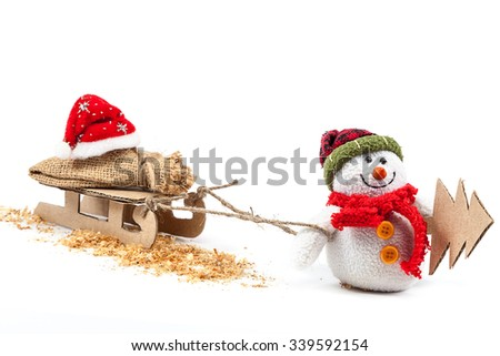Snowman with sledge, Christmas tree and Santa Claus clothes isolated on a white background. - stock photo