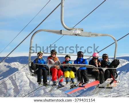 SNOWMASS, ASPEN, FEB 13: A family sitting on a ski chairlift and ready for skiing in a Ski resort in Snowmass near Aspen Colorado on a sunny day in Aspen, CO, Feb 13, 2016 - stock photo