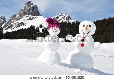 Snowmen against Alpine panorama