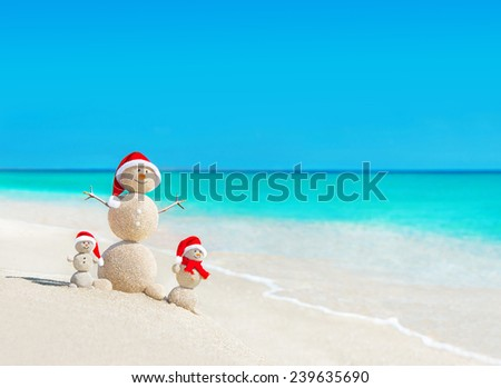 Snowmen family at tropical ocean beach in santa hats. New Years and Christmas holiday in hot countries concept. - stock photo