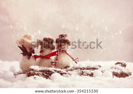 Snowmen having a gossip on a snow covered log - stock photo