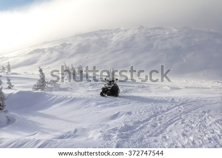 Snowmobile against a background of mountains in the Ural mountains.