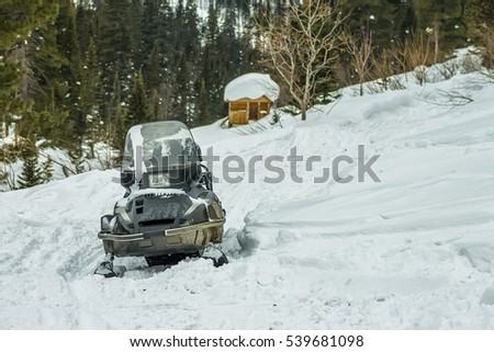 Snowmobile on the hillside against the backdrop of a wooden house in the woods.
