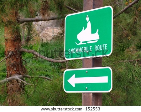 Snowmobile sign in spring in mountain community - stock photo
