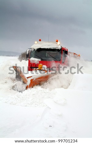 snowplow or plow clear snow of road during winter blizzard or storm