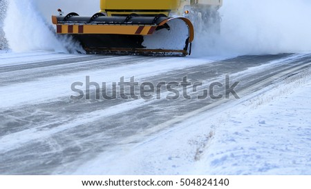 Snowplow removes snow off icy road in winter. Copy space for your text.