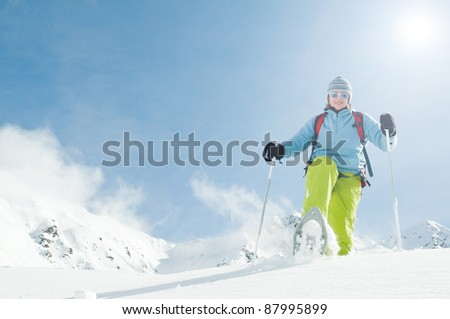 Snowshoeing -female with racket trekking in snow (space for text)