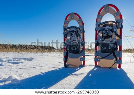 snowshoes cast a shadow on the fresh snow - stock photo