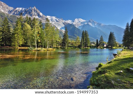 Snowy Alps picturesquely surrounded by evergreen trees and lake. Cozy urban park in Chamonix, Provence