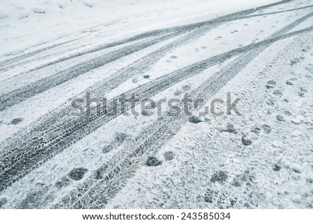 Snowy and icy city road with tire trace and many footprints. - stock photo