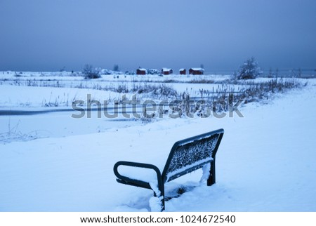Snowy bench in a park with some old cabins in the background at the swedish island Oland