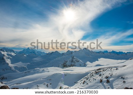 Snowy blue mountains in clouds. Winter ski resort - stock photo
