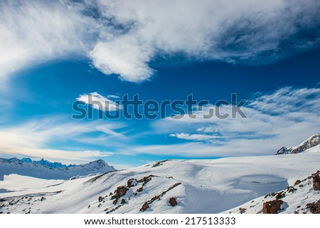 Snowy blue mountains in clouds. Winter ski resort