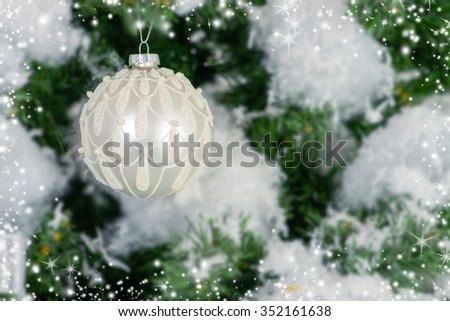 Snowy Christmas tree, decorated with a beautiful sparkling Christmas ball.