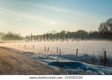 Snowy country landscape in low afternoon sunlight on a foggy day in the winter season. - stock photo