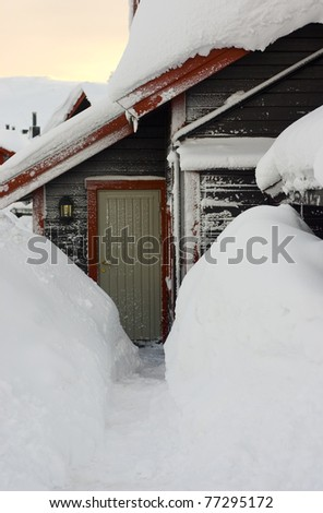 Snowy entrance to a ski cabine, digged path to the door - stock photo