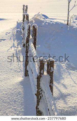 Snowy fence in winter garden - stock photo