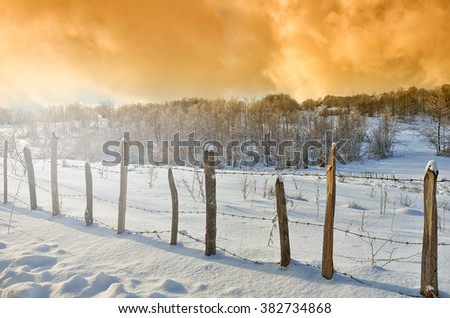 Snowy field with enclosure at sunset in winter - stock photo