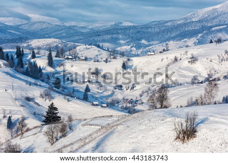 Snowy, frosty alpine winter landscape, panoramic view on the village, snowy wooden mountains and cloudy sky