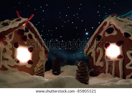 Snowy gingerbread cottage with stars in the background - stock photo