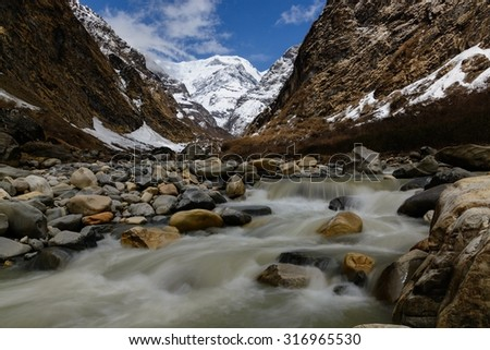 Snowy Himalayan Peak and the River - stock photo