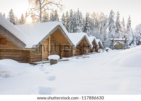 Snowy huts covered with snow at bright snowy day. Forest in background.