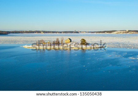Snowy island in the middle of the ice drift in the Baltic sea in Finland - stock photo