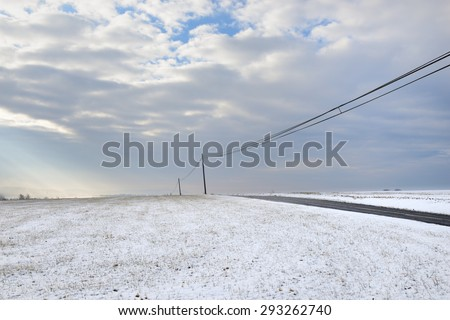 Snowy Landscape with Lonely Road and Dramatic Sky - stock photo