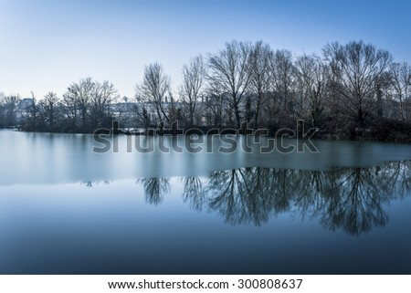 snowy mountain and trees reflected in the cold lake, National reserve of Sebino peat bog. These Torbiere are considered a priority area for biodiversity in the Po Valley in Lombardy, Italy.