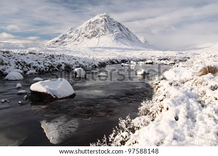 Snowy mountain landscape and river at Glencoe - stock photo