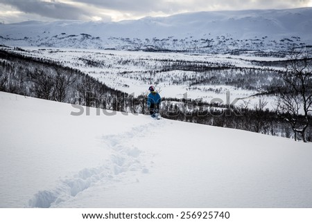 Snowy mountain landscape with a child walking, Nordland, Norway