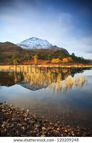 Snowy mountain reflected in Loch - stock photo