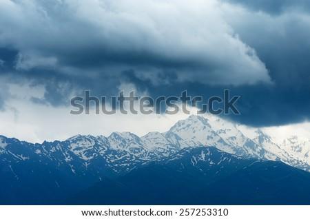 Snowy mountain ridge in the clouds. Georgia, Svaneti ridge - stock photo