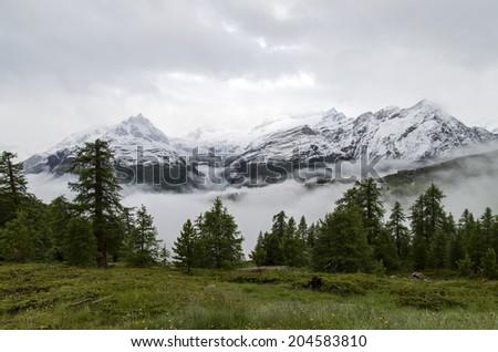 Snowy mountain tops in the Swiss Alps in July near the village of Zermatt Mountain background - stock photo