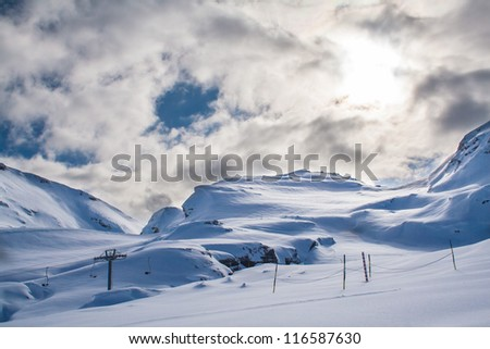 Snowy mountain with huge white cloud above and a ski lift in the foreground
