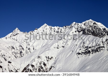 Snowy mountains and blue clear sky at sun day. Caucasus Mountains. Svaneti region of Georgia. - stock photo